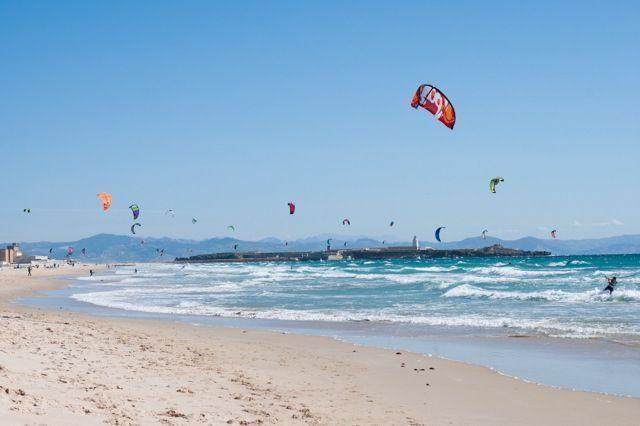 Gracias a los que practican kitesurf, el cielo parece llenarse de pájaros de colores sobrevolando el mar.